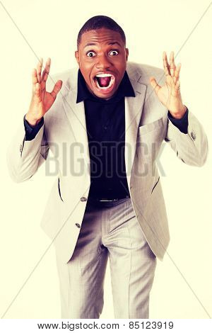 Angry and frustrated african businessman screaming.