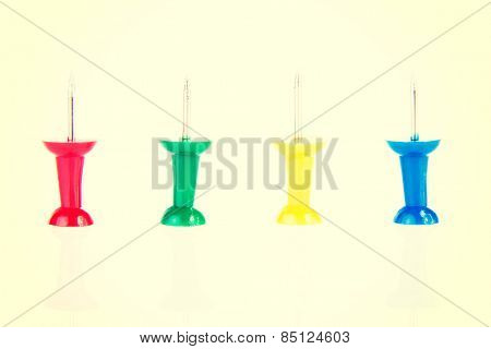 Four colorful office drawing pins.