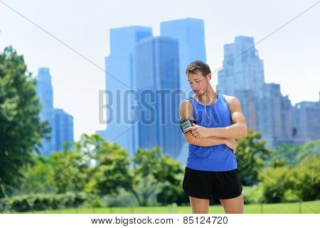 New York City man runner listening music on smartphone. Male adult jogger running using touchscreen on armband for workout in Central Park with urban background of Manhattan's skyscrapers skyline.