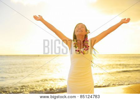 Happy carefree woman free in Hawaii beach sunset. Beautiful woman in the golden sunshine glow of sunset with arms outspread and face raised in sky enjoying peace, serenity in nature.