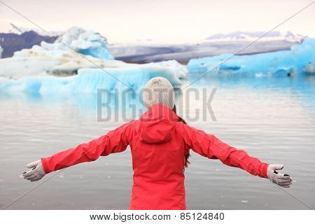Freedom happy woman at glacier lagoon on Iceland serene and blissful. Tourist girl serene enjoying view of Jokulsarlon glacial lake. Woman in beautiful Icelandic nature landscape looking at iceberg.