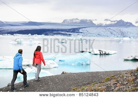Hiking couple on Iceland Jokulsarlon glacial lagoon / glacier lake. Active lifestyle tourists people walking enjoying beautiful Icelandic nature landscape with Vatnajokull in backround.