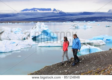 People hiking on Iceland Jokulsarlon glacial lagoon / glacier lake. Active lifestyle couple tourists walking enjoying beautiful Icelandic nature landscape with Vatnajokull in backround.