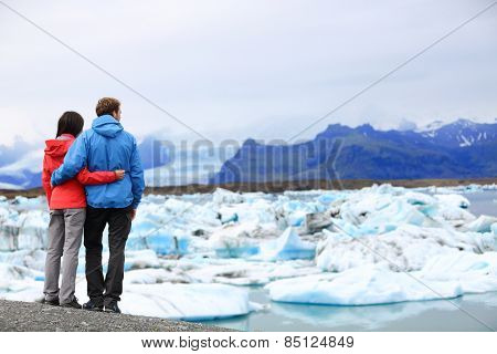 Tourists couple romantic on Iceland Jokulsarlon glacial lagoon / glacier lake. Active lifestyle woman and man enjoying view of beautiful Icelandic nature landscape with Vatnajokull in backround.
