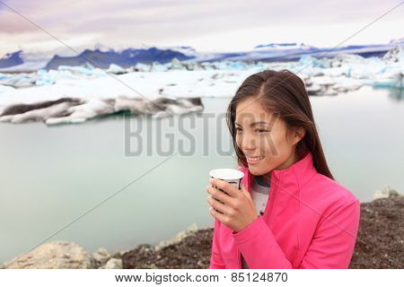 Woman drinking coffee on travel trip at glacier lagoon on Iceland. Happy tourist woman enjoying view of Jokulsarlon glacial lake. Smiling woman in beautiful Icelandic nature landscape with icebergs.