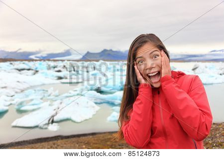 Excited happy woman at glacier lagoon on Iceland making funny face expression. Happy tourist woman by Jokulsarlon glacial lake in beautiful Icelandic nature landscape with icebergs.