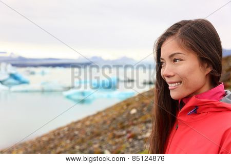 Woman at glacier lagoon on Iceland. Happy tourist woman looking enjoying view of Jokulsarlon glacial lake. Smiling woman in beautiful Icelandic nature landscape looking at iceberg.
