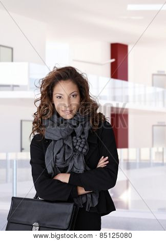 Trendy casual female office worker at business center, standing, smiling, arms crossed, looking at camera.