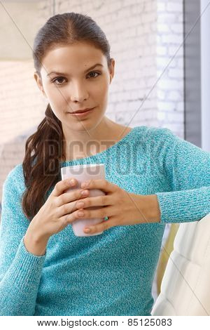 Confident young casual caucasian woman with mug in hand at home. Cupping, small smile, looking at camera.