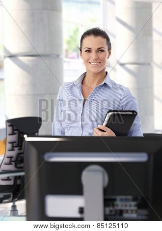 Portrait of happy mid adult casual brunette caucasian secretary at business office. Smiling, looking at camera, focus in background.