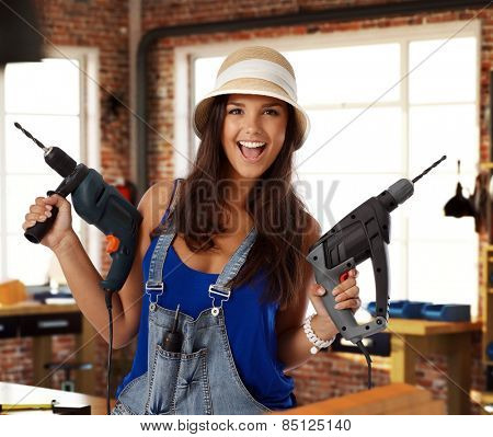 Happy young caucasian casual woman holding power drill at workshop. Smiling, looking at camera, standing.