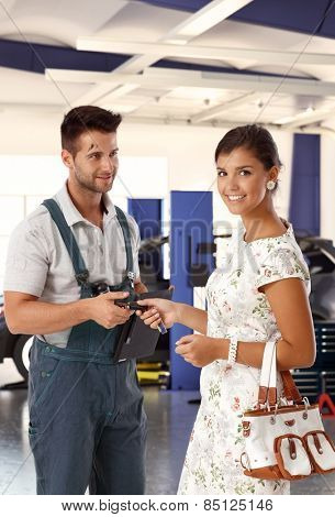 Happy attractive caucasian young woman at auto repair business shop, giving car keys to handsome dirty male mechanic. Smiling standing looking at camera.