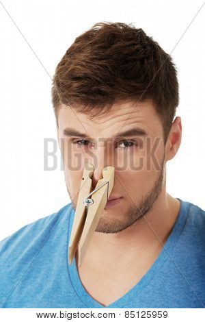 Young handsome man with clothespin on his nose.