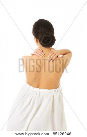 Back view woman wrapped in towel touching her back.