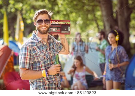 Handsome hipster holding retro cassette player at a music festival