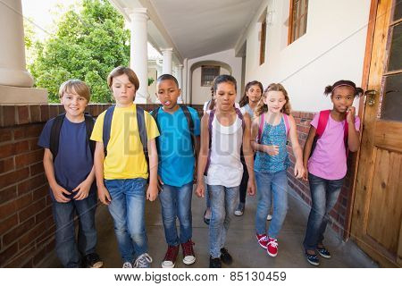 Cute pupils walking down the hall at the elementary school