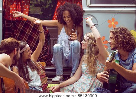 Hipster friends by camper van at festival on a summers day