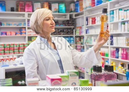 Cheerful pharmacist holding medication in the pharmacy