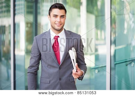Smiling businessman holding a newspaper under his arm