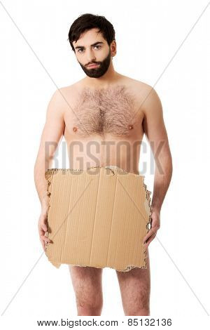 Shirtless man with a piece of cardboard begging for help.