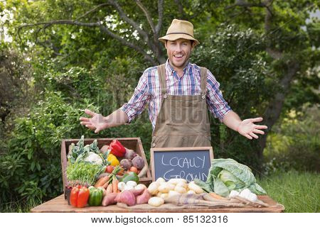 Happy farmer showing his produce on a sunny day