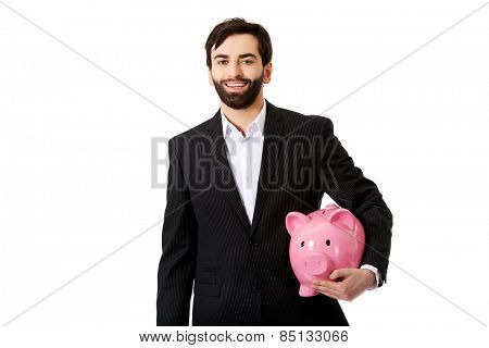 Happy handsome businessman holding a piggybank.