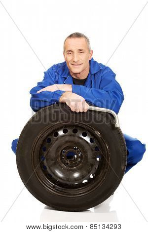 Happy mechanic with a tire and wrench.