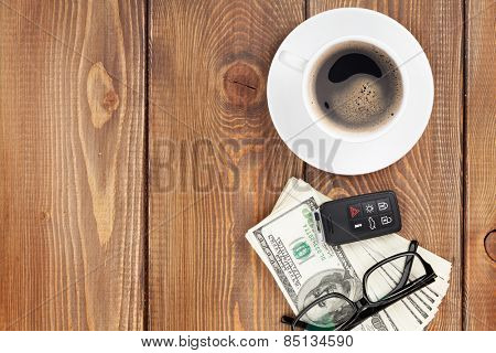 Money cash, glasses, car remote and coffee cup on wooden table with copy space