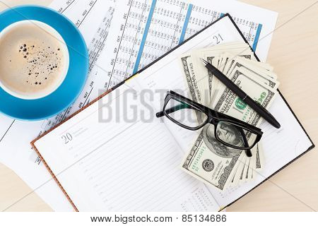 Office desk with reports, blank notepad and money cash. View from above with copy space