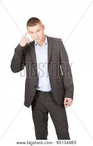 Young businessman gesturing with finger against temple