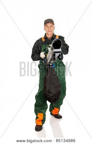 Experienced gardener in uniform with a leaf blower
