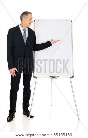 Mature businessman presenting something on flip chart.