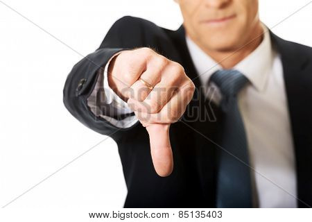 Close up on businessman hand showing thumb down sign.