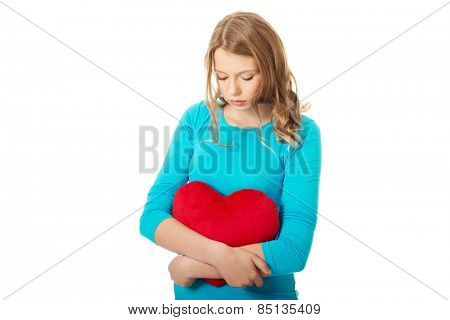 Worried teenage woman with heart shaped pillow