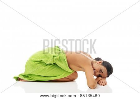 Spa woman curled up wrapped in towel