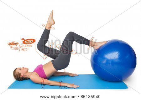 Side view of a fit woman exercising with fitness ball against fitness interface