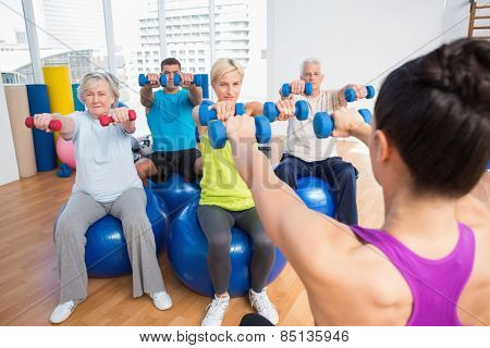 Female instructor with class lifting dumbbells in fitness studio