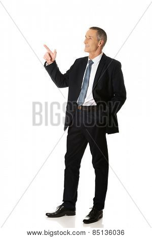 Side view businessman pointing upwards.