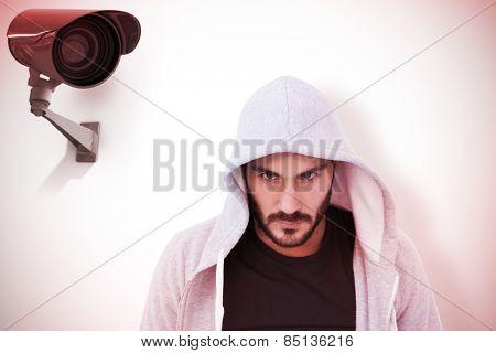 Portrait of dangerous man wearing hooded jacket against cctv camera