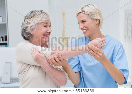 Happy female nurse assisting senior patient in raising arm at clinic