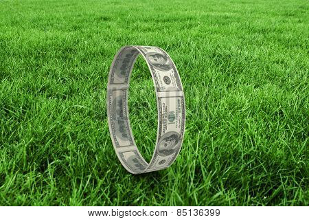 Wheel of dollars against grass