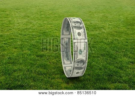 Wheel of dollars against green field