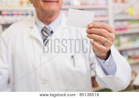 Senior pharmacist reading calling card in the pharmacy