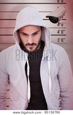 Portrait of dangerous man wearing hooded jacket against mug shot background