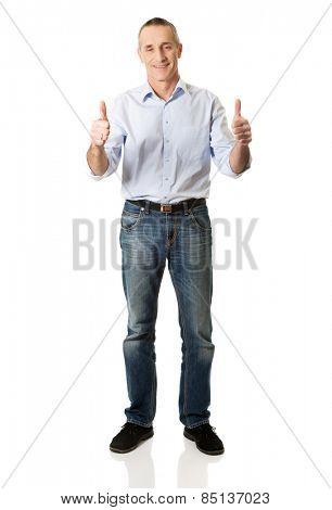 Smiling mature man gesturing ok sign.