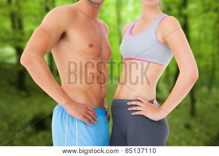 Mid section of a fit young couple against trees in the autumnal forest