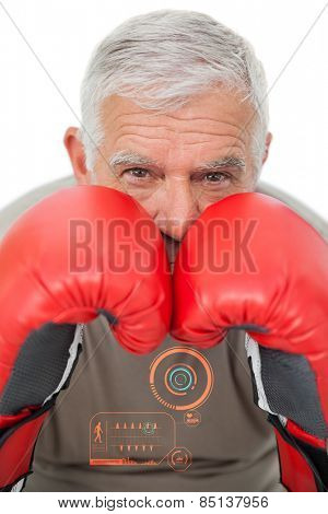 Close-up portrait of a determined senior boxer against fitness interface