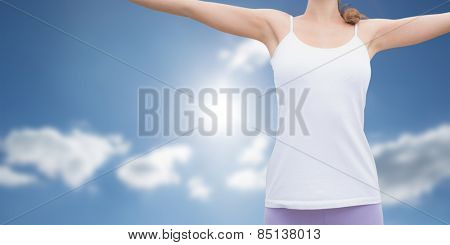 Woman standing with arms raised on countryside landscape against cloudy sky with sunshine