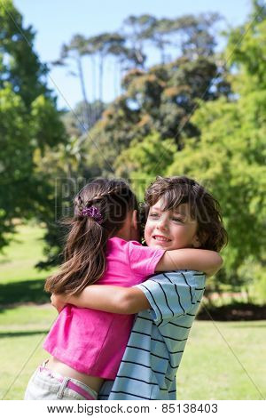 Little siblings hugging each other on a sunny day