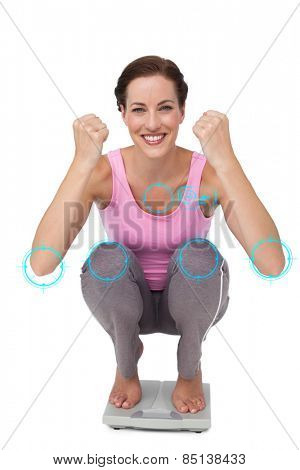 Portrait of a young woman cheering on weight scale against fitness interface